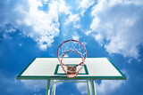 Basketball hoop on a blue sky with clouds.