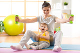 Slim mother with little kid doing gymnastics and fitness exercises.