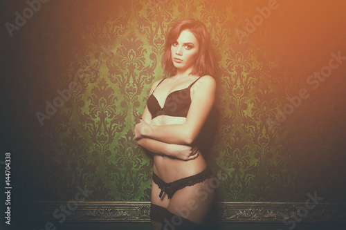Sexy redhead in lingerie on vintage green wall posing sensual to camera Poster