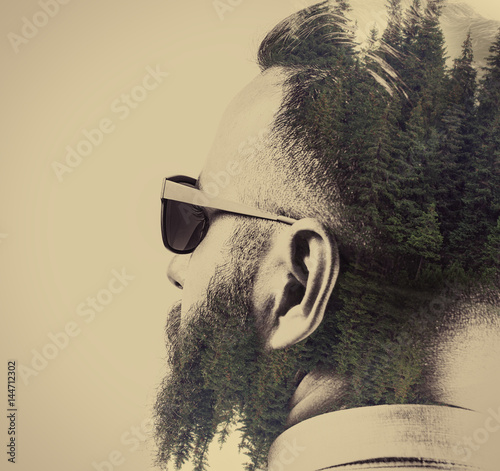 Portrait of a bearded man in sunglasses, with a stylish haircut. Black and white. Image created using multiple exposures. Forest landscape is depicted on dark parts of image. - 144712302