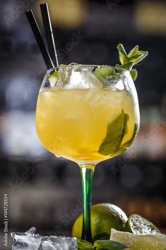Cocktail garnished with a lime slice and mint leaf