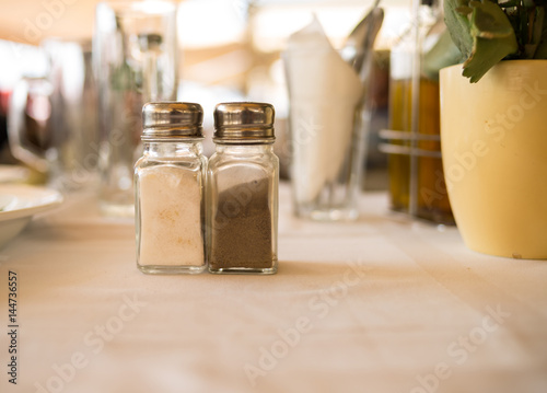 Spoed canvasdoek 2cm dik Pizzeria Spices salt pepper in transparent vessels stand on a table laid white with a tablecloth close-up