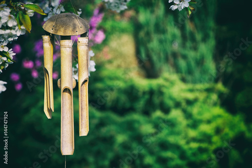 wind chimes hanging in a blooming tree, bamboo chimes in a garden