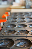 Close-up detail of multiple empty Taiyaki molds on a stove at a shop. Vertical orientation. Kyushu, Japan. Travel and cuisine concept.