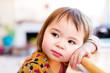 Toddler girl leaning against table