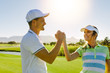 Male and female friends giving high-five at golf course