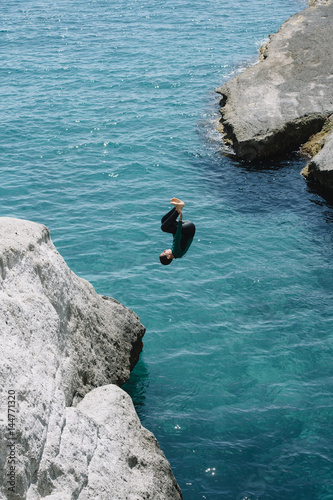 Boy jumping to the sea from the stone Poster