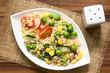 Bunter Vollkornreissalat mit Kirschtomaten, Mais, Gurke, Radieschen und Erbsen serviert auf Teller, fotografiert mit natürlichem Licht