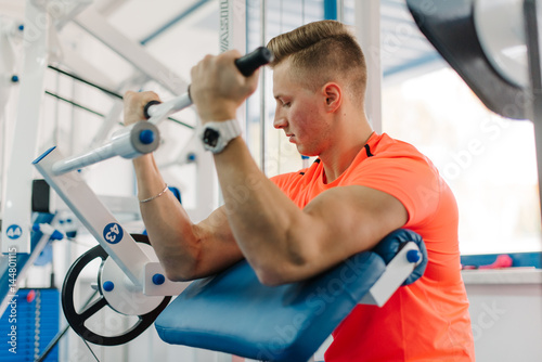 young attractive athletic guy training his biceps looking at it Poster