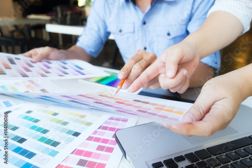 Artist drawing on graphic tablet with color swatches in office. Poster