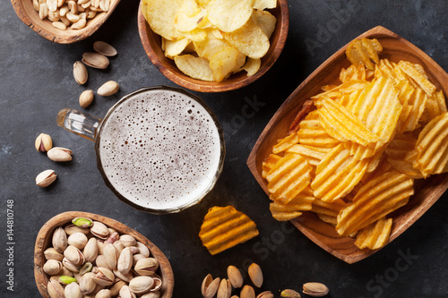 Lager beer and snacks on stone table Poster