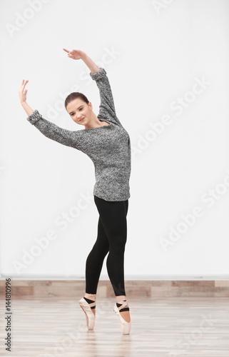 Plexiglas Ballet art concept. Young beautiful ballerina training in dance hall
