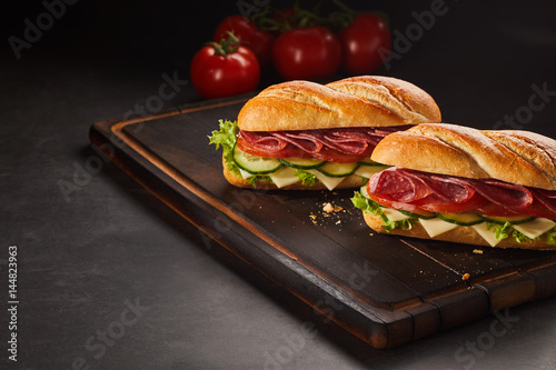 Two pepperoni sandwiches with cheese and cucumber Poster