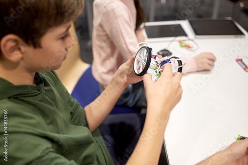 boy building robot at robotics school