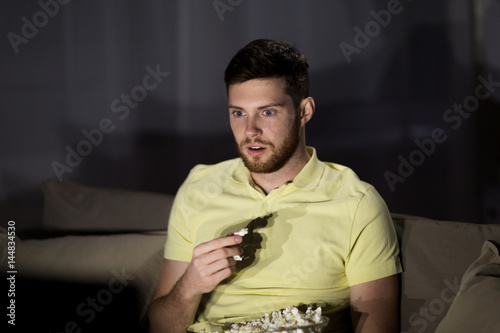 man watching tv and eating popcorn at night Poster