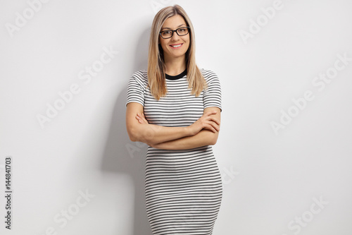 Plakat Young woman in a dress leaning against a white wall