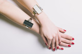 Female hands with red nails and bracelets