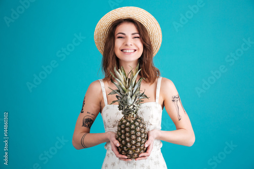 Poster Happy young lady standing isolated holding pineapple