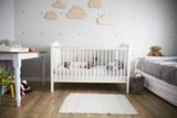 Side View Of Baby Girl Sleeping In Nursery Cot - 144860593