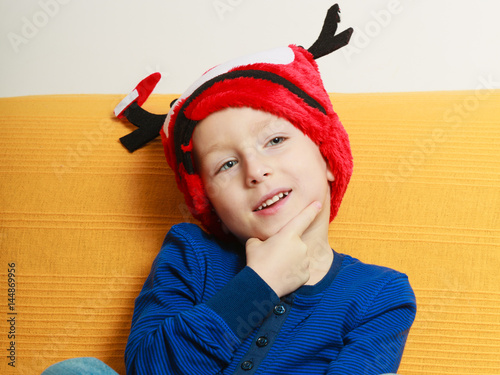 Little boy on sofa wearing christmas hat Poster