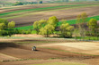 Farmer in tractor preparing land with seedbed cultivator, spirng, countryside in Ponidzie, Poland