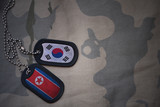army blank, dog tag with flag of south korea and north korea on the khaki texture background. military concept