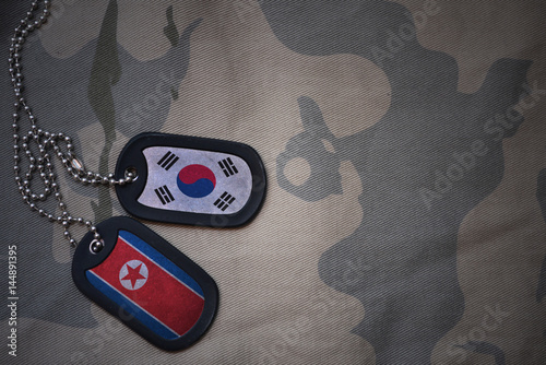 Aluminium Seoel army blank, dog tag with flag of south korea and north korea on the khaki texture background. military concept