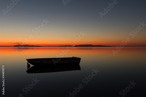 A warm sunset on a calm water, with Islands in the background