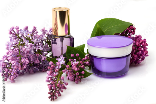 Cosmetic face care products and lilac flowers isolated on white background. Cream, fluid, serum.