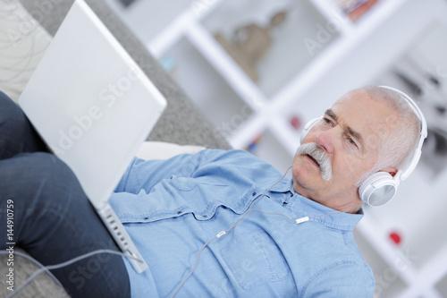 senior man listening to music with headphones Poster