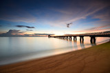 Long exposure shot of seascape with long jetty background at dusk.