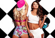 Fashion beautiful young brunette and blond models in rnb style clothes with pink colorful baseball cap posing near chess wall
