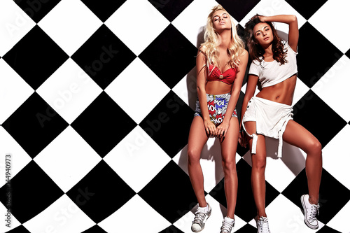 Fashion beautiful young brunette and blond models in rnb style clothes with pink Poster