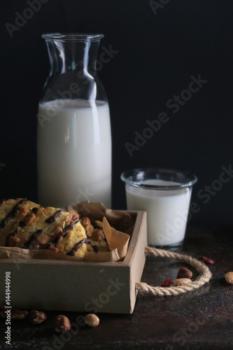 Chocolate cookies with nuts in wooden box. Bottle and glass of milk.