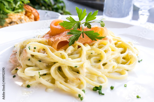 tasty pasta with salmon on a the table - 144952390