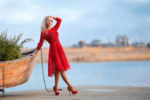 Woman in red dress at the river pier