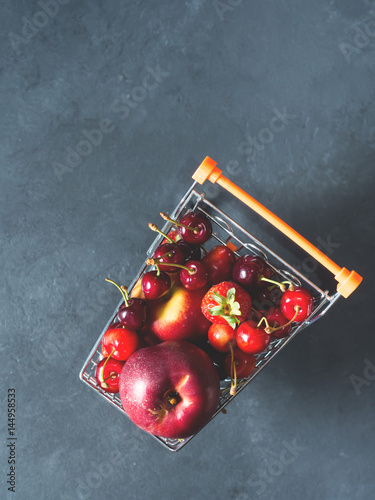 Fresh red fruit and berries - cherries, peaches and strawberries - in supermarket cart tray on black background. Copy space - 144958533