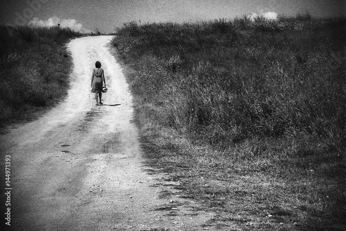 Woman silhouette walking up the hill dirt road on a scorching  heat - 144971393