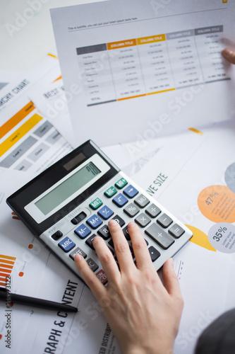 Closeup of Marketing Expert Hand Using Calculator - 144973122