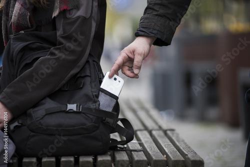 Dieb stiehlt smartphone aus einer Tasche - 144976104
