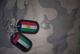 army blank, dog tag with flag of kurdistan and united arab emirates on the khaki texture background. military concept