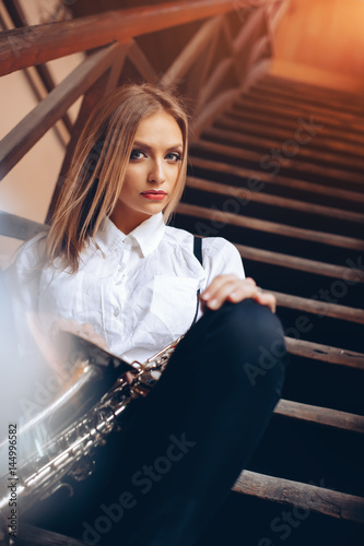 Plakát Young attractive girl sitting on steps in white shirt with a saxophone - outdoor