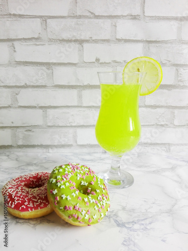 Poster Donuts on a marble countertop with lemon drink