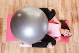 Young lady lying on the mat with fit ball.