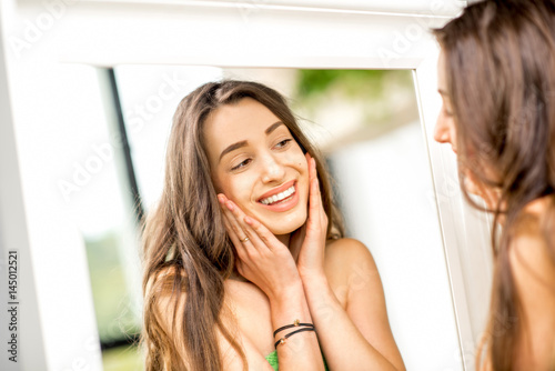Poster Pretty woman looking at the mirror with a smile standing in towel in the bathroo
