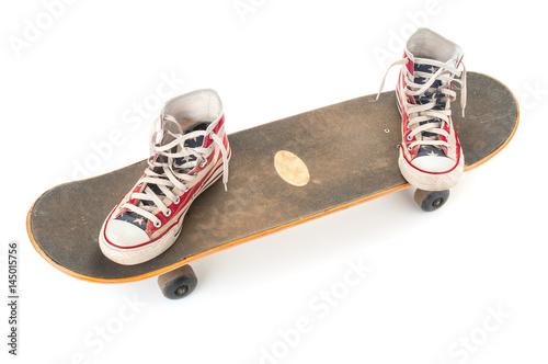 Fotobehang Skateboard Old skateboard and gumshoes on white background