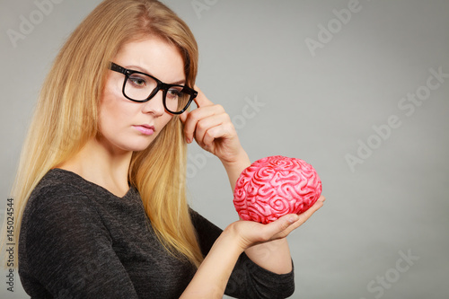 Woman thinking and holding fake brain Poster
