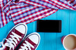 Burgundy sneakers, cellphone, coffee, checkered shirt on bright turquoise background, free space for advertisement or text
