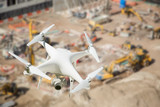 Unmanned Aircraft System (UAV) Quadcopter Drone In The Air Over Construction Site. - 145027729