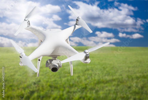 Unmanned Aircraft System (UAV) Quadcopter Drone In The Air Over Grass